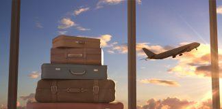 Koffers en opstijgend vliegtuig in de lucht