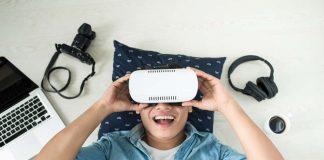 Lachende jongen met VR bril en gadgets om zich heen