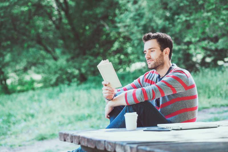 Man die een boek aan het lezen is in het park