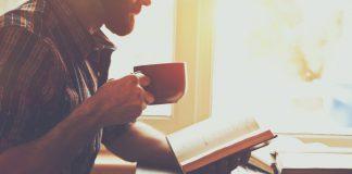 Man met koffie die een boek leest