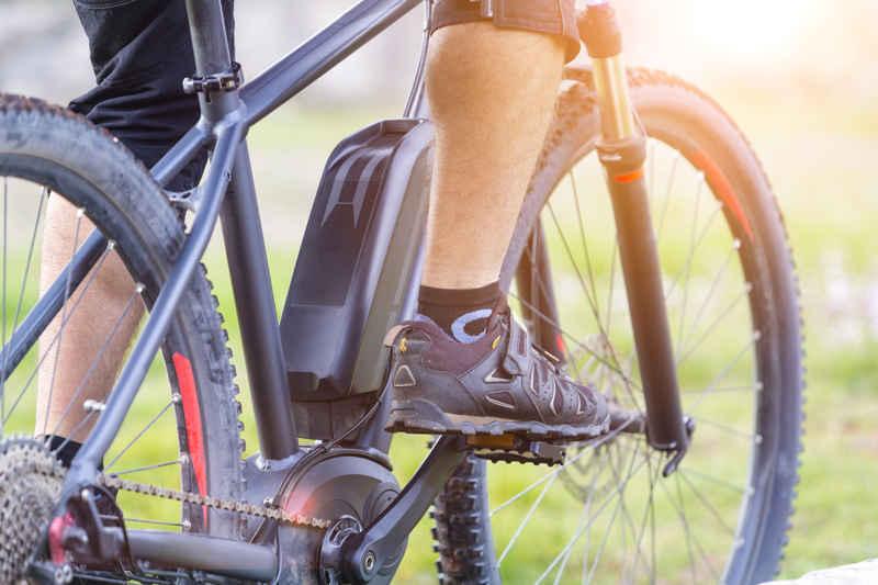 Man op elektrische fiets met accu op frame