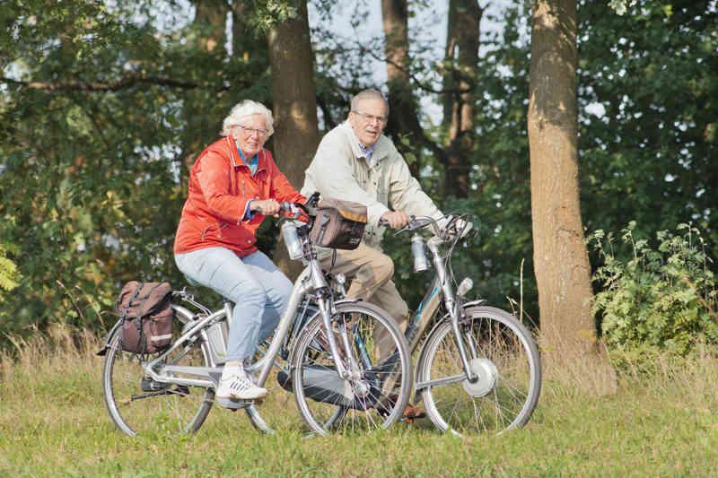 Oudere man en vrouw op een elektrische fiets