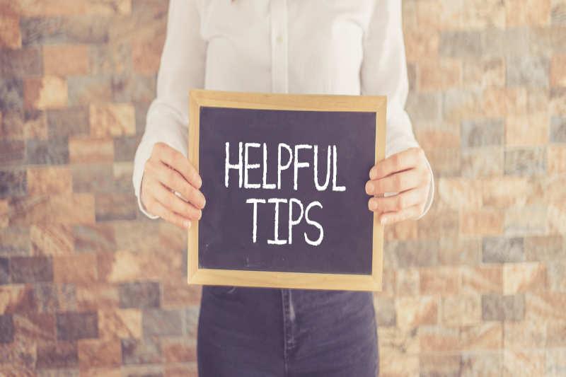 Vrouw die een bord laat zien met Helpful Tips