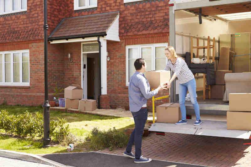 Vrouw en man die een verhuis wagen aan het uitladen zijn in hun nieuwe woning