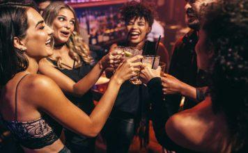 vrienden lachend en proostend op een feestje