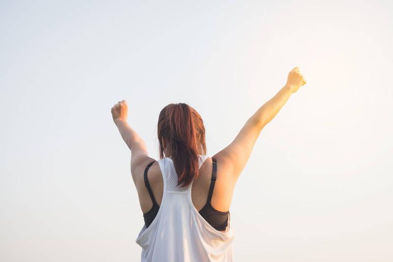 Vrouw met haar armen in de lucht, winning yeah!