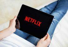 man op een tablet die Netflix afspeeld
