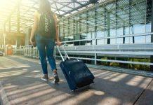 vrouw op het vliegveld met reiskoffer